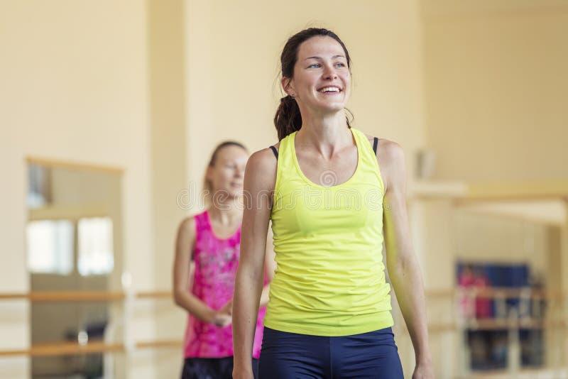 Усмехаясь женщины в спортзале на разминке в спортзале стоковое изображение