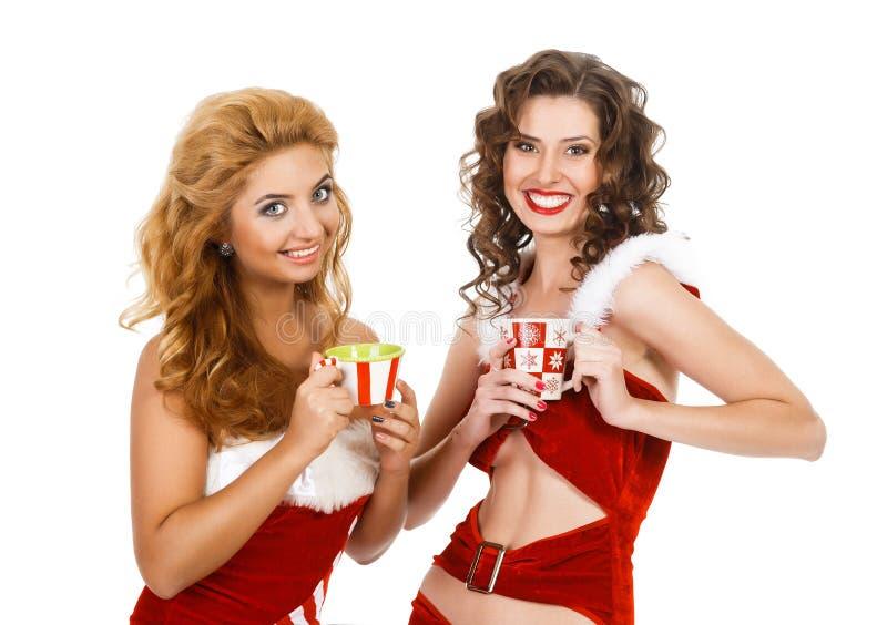 Усмехаясь женщины рождества с чаем спаривают нося одежды santa стоковая фотография