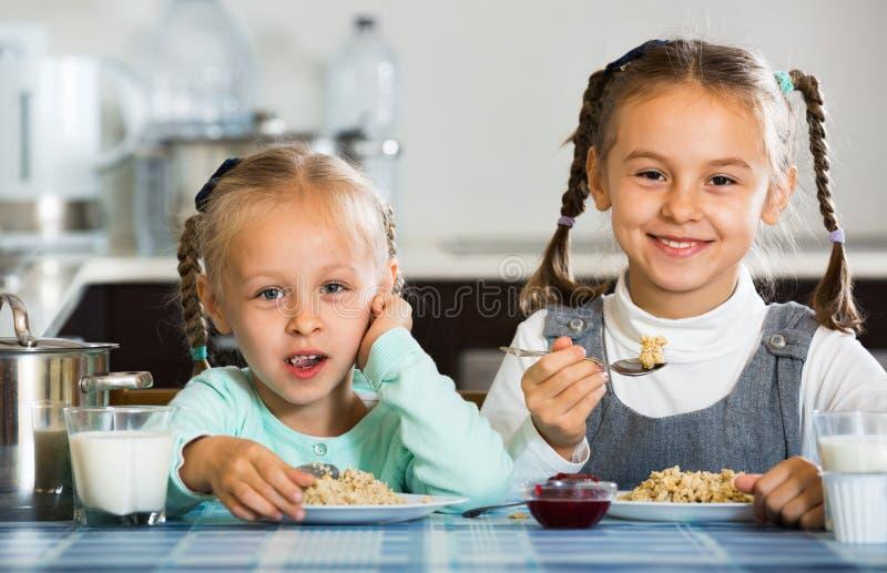 2 усмехаясь жизнерадостных девушки есть здоровую овсяную кашу стоковые фото