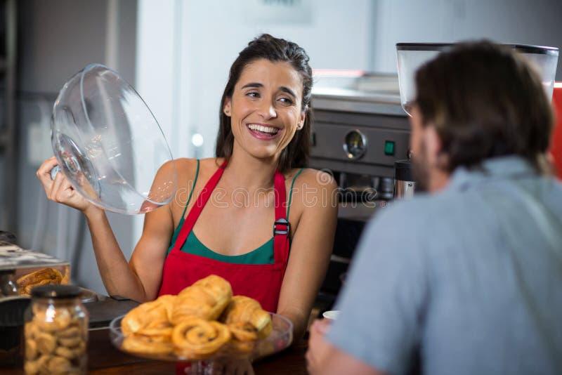 Усмехаясь закуски хлебопекарни сервировки женского персонала к мужскому клиенту на счетчике стоковое фото