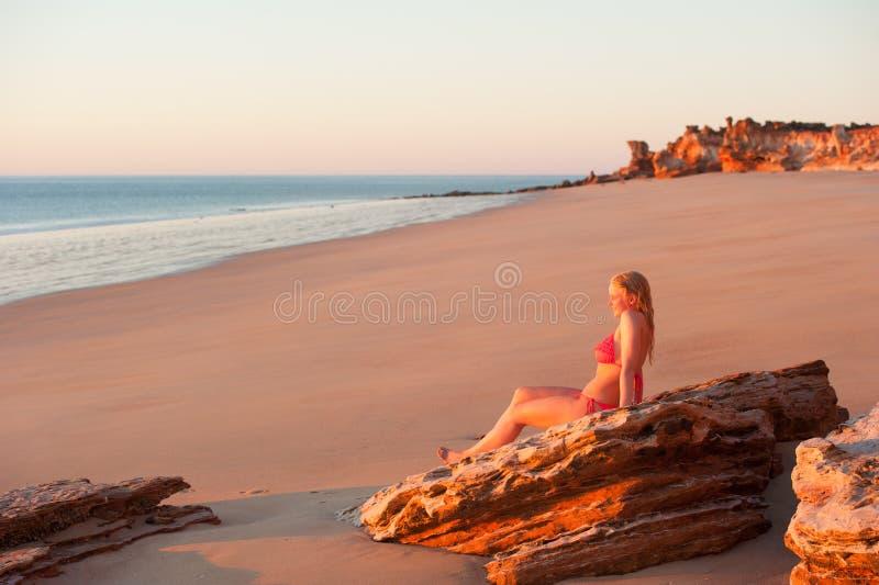 Усмехаясь заход солнца пляжа молодой женщины тропический стоковое фото