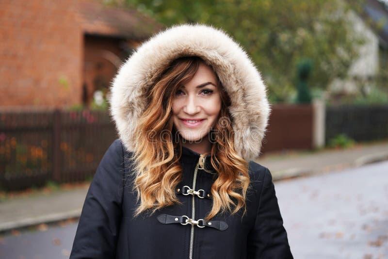 Усмехаясь зима молодой женщины нося покрывает с поддельным клобуком меха стоковая фотография rf