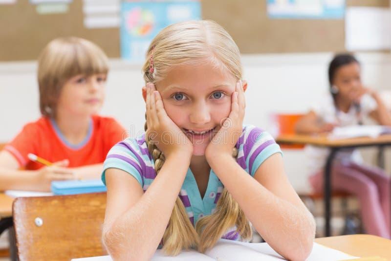 Усмехаясь зрачок сидя на ее столе стоковое изображение