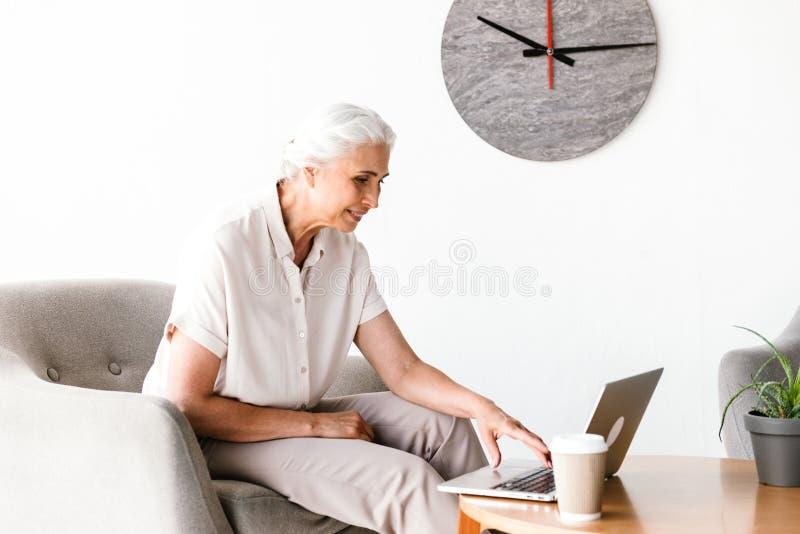 Усмехаясь зрелая бизнес-леди работая на компьтер-книжке стоковые фотографии rf