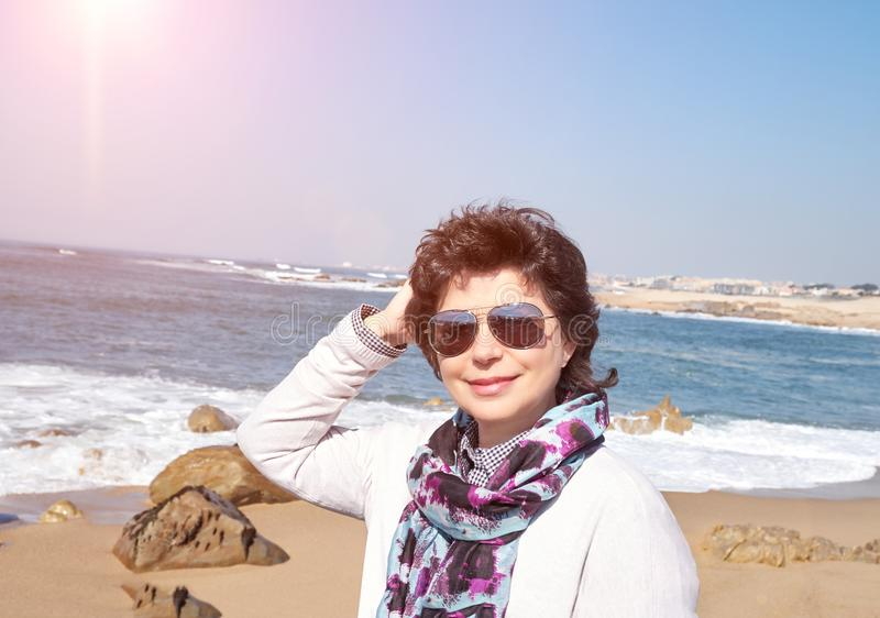 Усмехаясь зрелая женщина 50 лет на пляже стоковые изображения