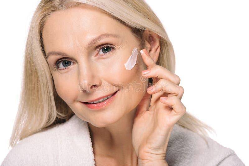 усмехаясь зрелая женщина прикладывая косметическую сливк стоковое изображение rf