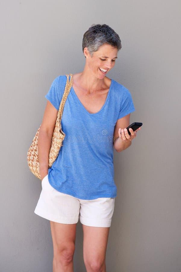Усмехаясь зрелая женщина смотря мобильный телефон стоковые изображения rf