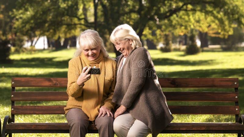 Усмехаясь зрелые дамы наблюдая фото или новости на смартфоне сидя в парке стоковые фото