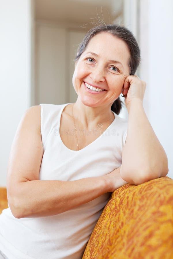 Усмехаясь зрелая женщина в доме стоковая фотография rf