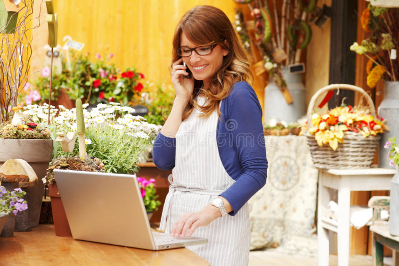 Усмехаясь зрелое предприниматель цветочного магазина мелкого бизнеса флориста женщины