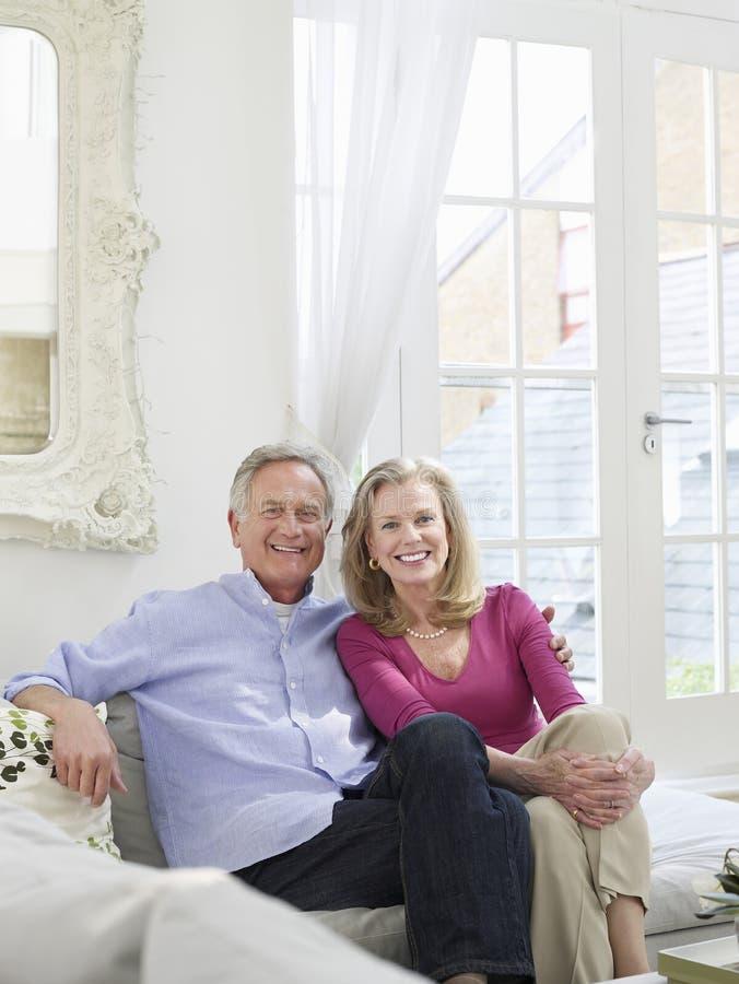Усмехаясь зрелые пары в белом домашнем интерьере стоковые фотографии rf