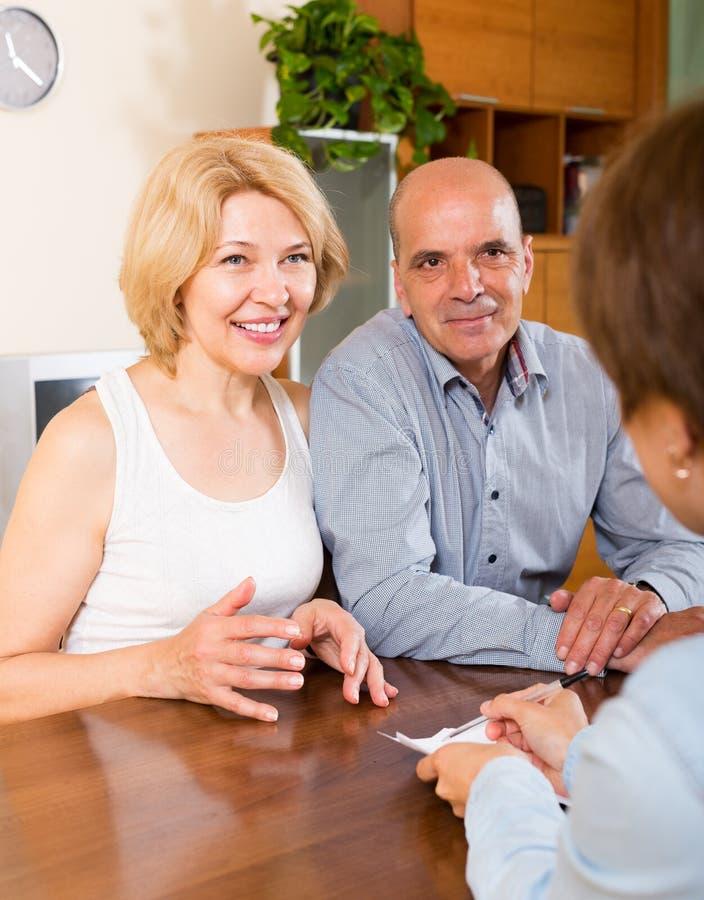 Усмехаясь зрелые пары пенсионеров разговаривая с работником стоковые фотографии rf