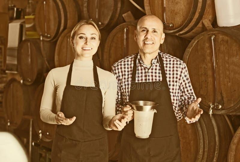 Усмехаясь зрелые человек и молодая женщина представляя с вином от древесины стоковое фото rf