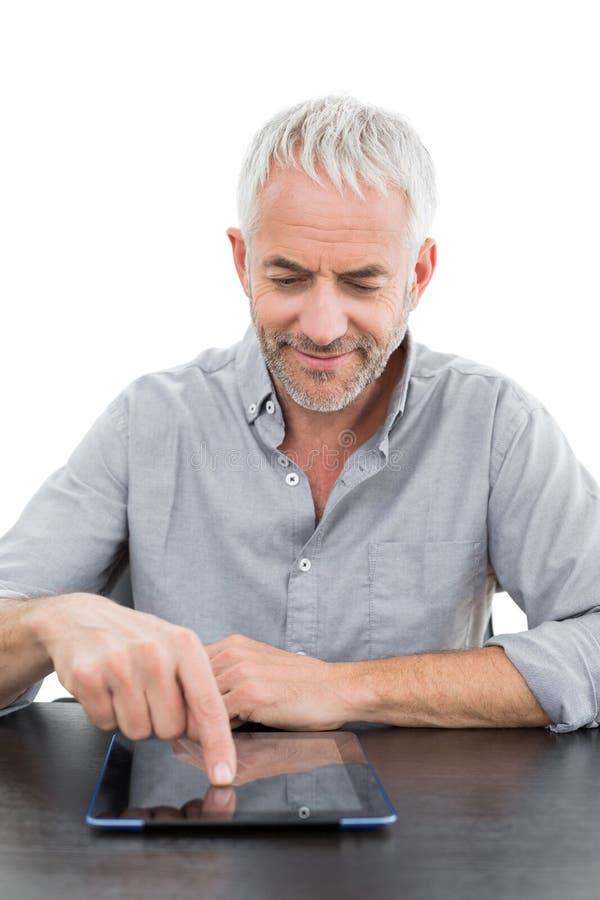 Усмехаясь зрелый бизнесмен используя цифровую таблетку на столе стоковая фотография