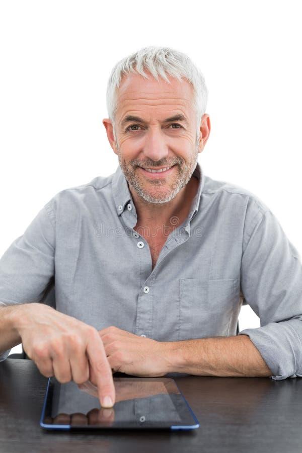 Усмехаясь зрелый бизнесмен используя цифровую таблетку на столе стоковые фото