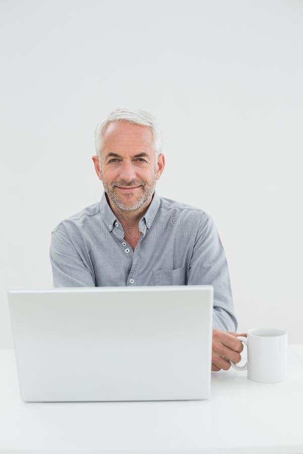 Усмехаясь зрелый бизнесмен с компьтер-книжкой и кофейной чашкой стоковые изображения rf