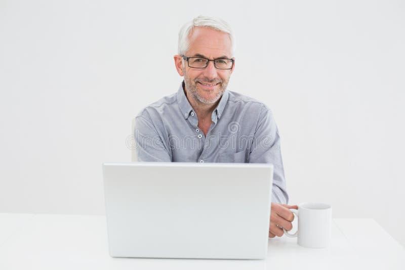 Усмехаясь зрелый бизнесмен с компьтер-книжкой и кофейной чашкой стоковые фото