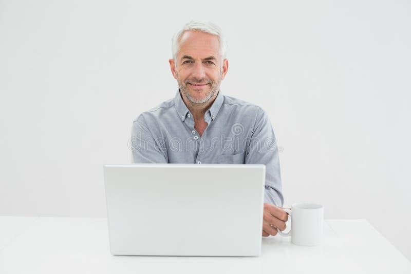 Усмехаясь зрелый бизнесмен с компьтер-книжкой и кофейной чашкой стоковая фотография rf