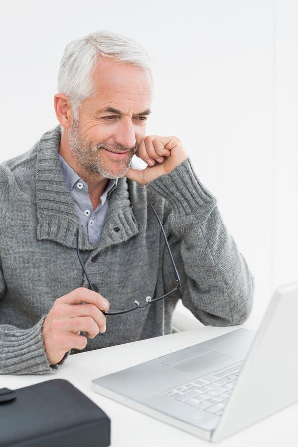 Усмехаясь зрелый человек используя компьтер-книжку на столе стоковая фотография rf