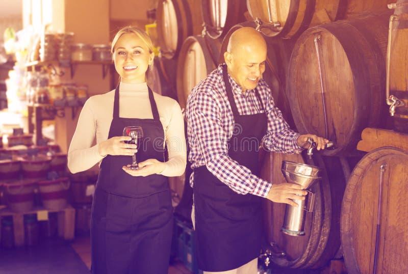 Усмехаясь зрелый человек и молодой женский представлять с вином от древесины стоковые изображения