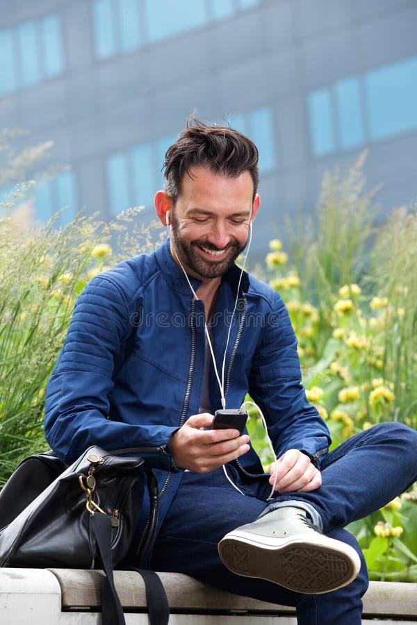Усмехаясь зрелый человек слушая к музыке на мобильном телефоне стоковые фото