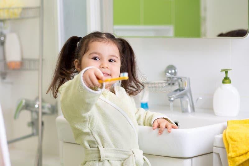 Усмехаясь зубы маленькой девочки чистя щеткой в ванне стоковое фото rf