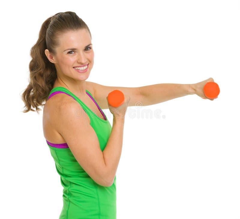 Усмехаясь здоровая молодая женщина делая тренировку с гантелями стоковая фотография rf