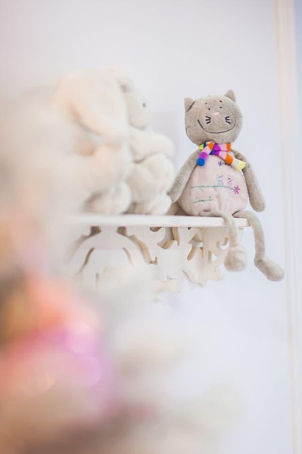 Усмехаясь игрушка кота плюша сидит на белом шкафе стоковая фотография rf