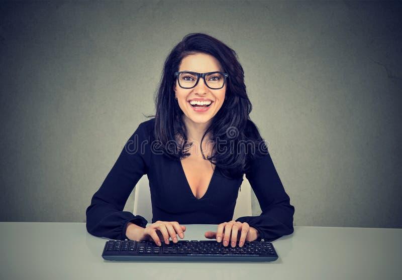 Усмехаясь изумленная женщина печатая на клавиатуре компьютера стоковое изображение rf