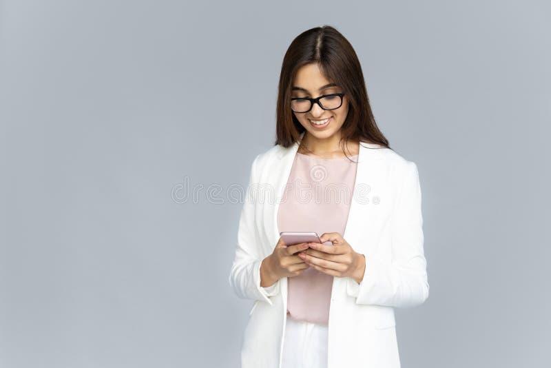 Усмехаясь индийская молодая бизнес-леди используя телефон изолированный на предпосылке стоковые фото