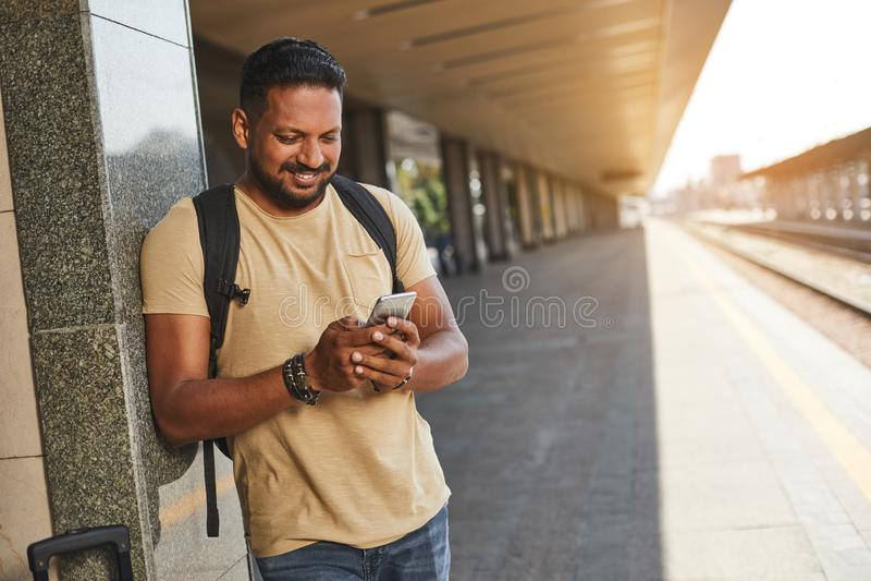 Усмехаясь индусский человек используя его телефон на платформе стоковая фотография
