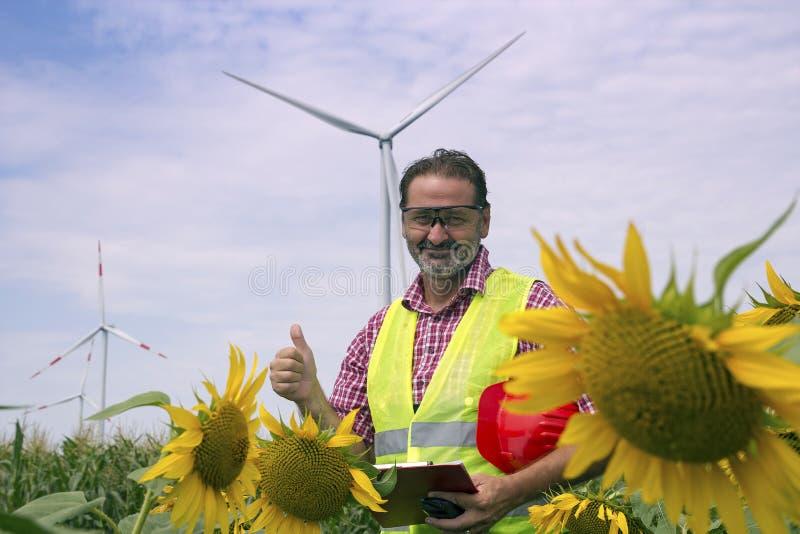 Усмехаясь инженер при большой палец руки вверх стоя против ветровой электростанции стоковые изображения rf