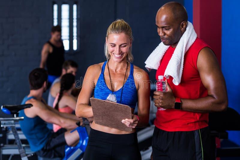 Усмехаясь инструктор фитнеса обсуждая с человеком в спортзале стоковое фото rf