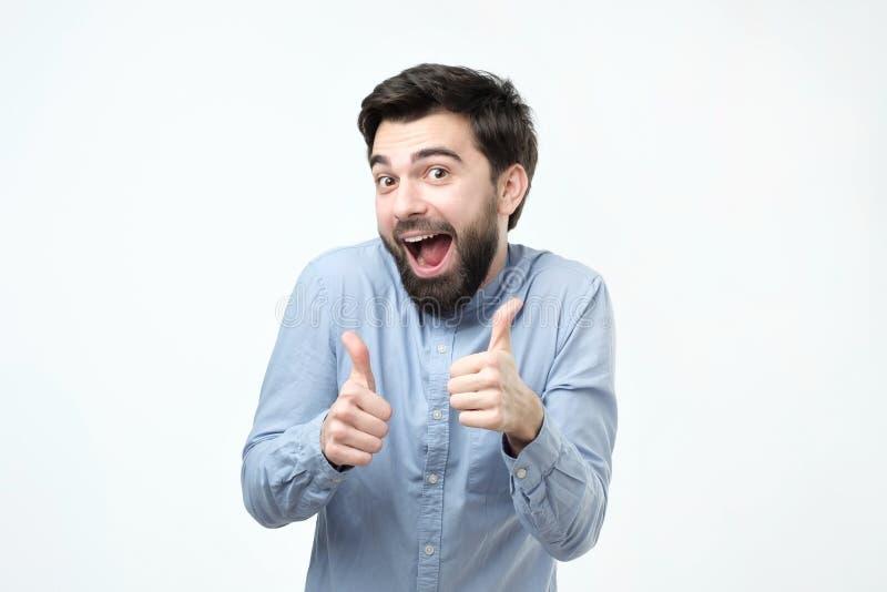 Усмехаясь испанский человек показывая оба большого пальца руки вверх и смотреть камеру стоковые фото