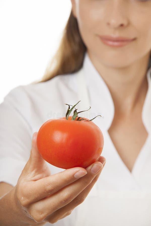Усмехаясь кашевар женщины с красным томатом стоковые изображения rf