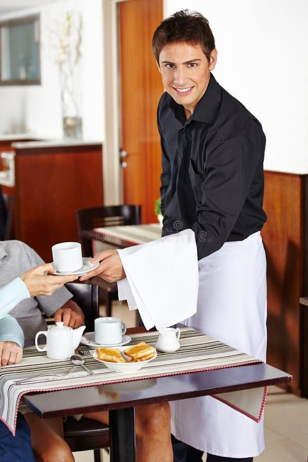 Усмехаясь кельнер в кофейне стоковое изображение rf