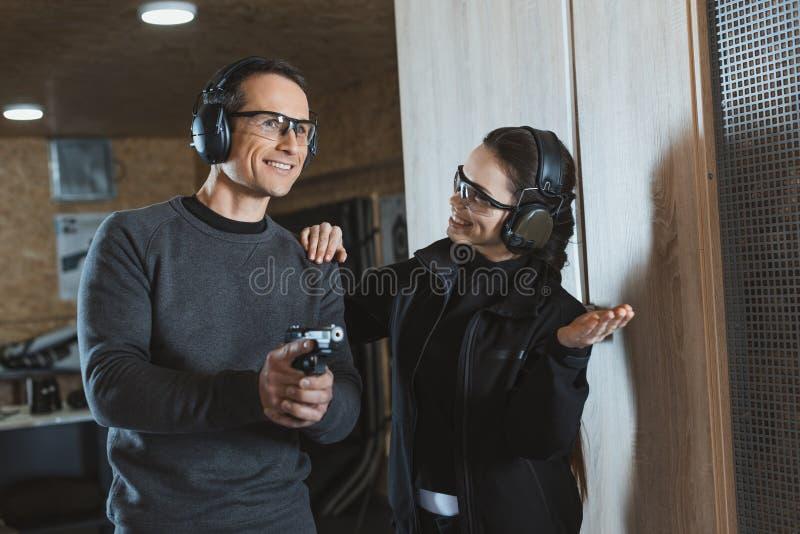 усмехаясь клиент инструктора стрельбы поддерживая стоковая фотография