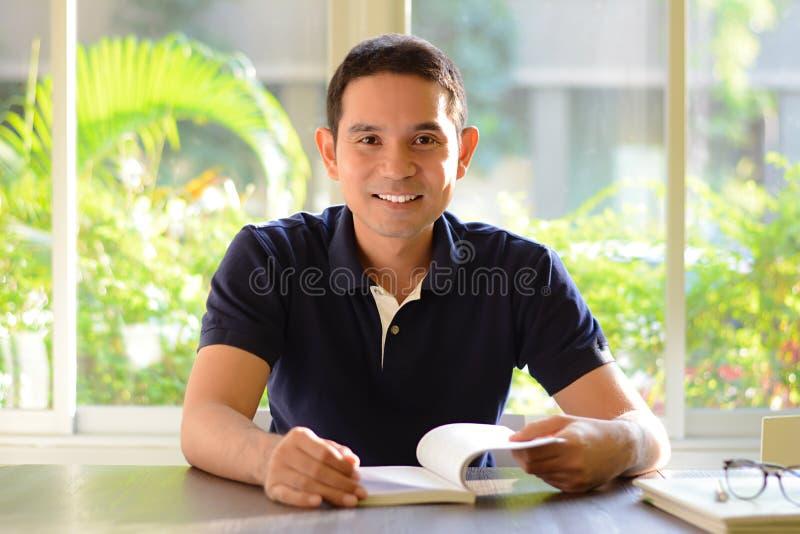 Усмехаясь книга отверстия человека на таблице стоковое фото rf