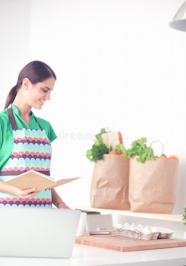 Усмехаясь книга чтения молодой женщины в кухне дома стоковое фото