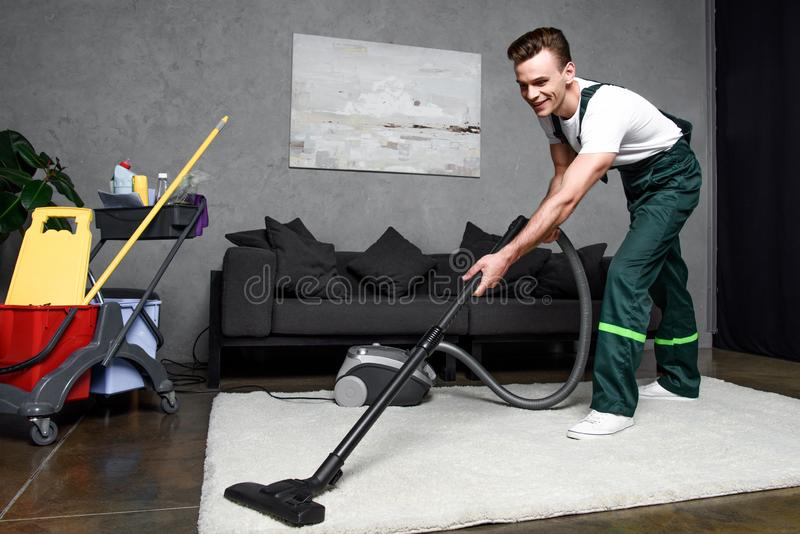 усмехаясь ковер молодого профессионального уборщика очищая стоковые изображения