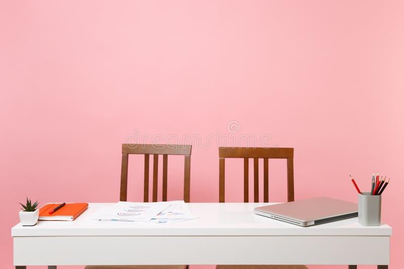 2 усмехаясь коллеги человека бизнес-леди сидят работа на белом столе с современным изолированным ноутбуком на пастельной розовой  стоковое фото