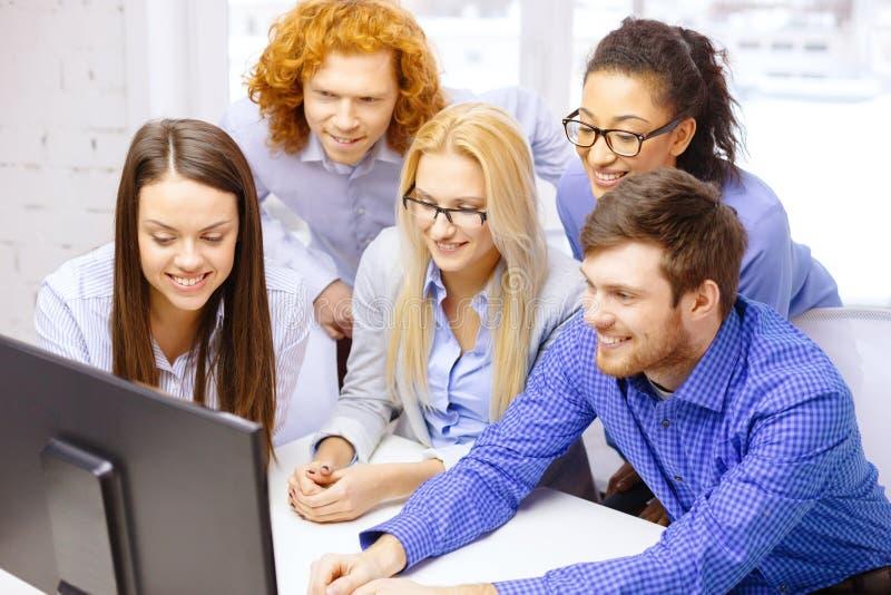 Усмехаясь команда дела смотря монитор компьютера стоковые изображения rf