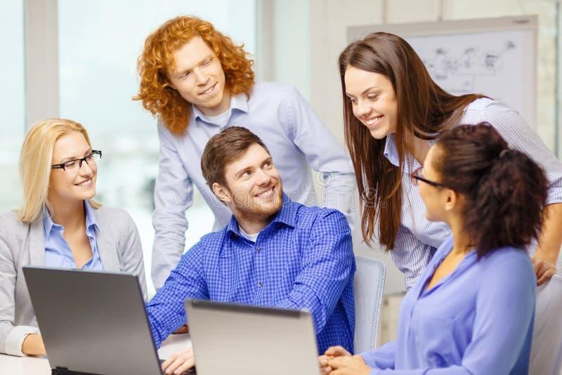 Усмехаясь команда с портативными компьютерами в офисе стоковое изображение