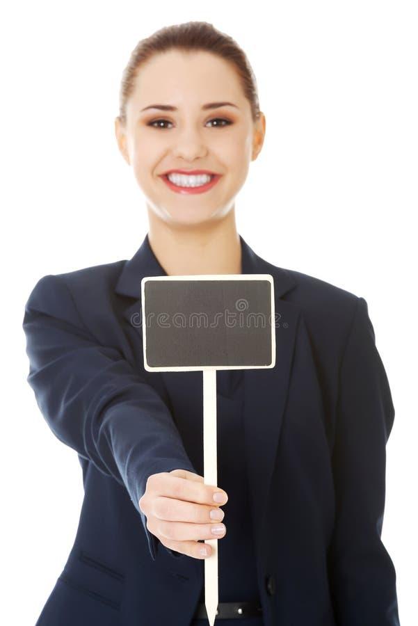 Усмехаясь коммерсантка держа малую пустую доску стоковое изображение