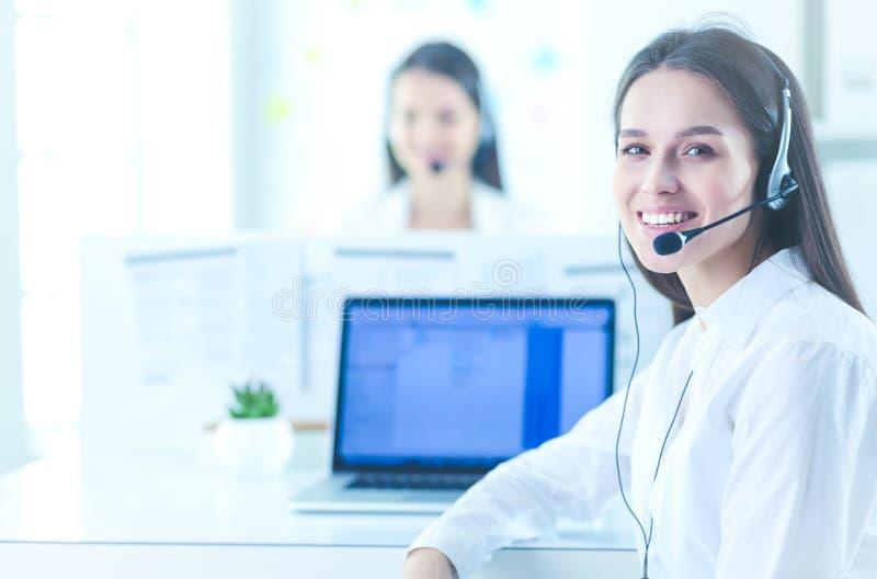 Усмехаясь коммерсантка или оператор линии для помощи со шлемофоном и компьютером на офисе стоковое изображение