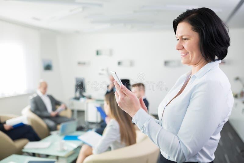 Усмехаясь коммерсантка используя smartphone в офисе стоковое фото