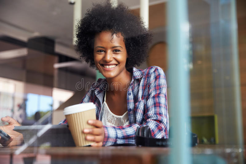 Усмехаясь коммерсантка используя таблетку цифров в кофейне стоковое изображение