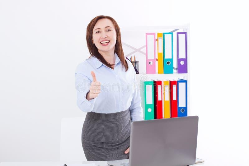 Усмехаясь коммерсантка и большой большой палец руки вверх изолированные на белой предпосылке на офисе белизна успеха дела изолиро стоковая фотография