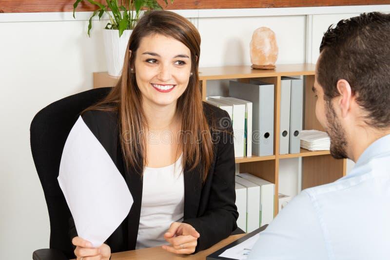 Усмехаясь коммерческий директор женщины разговаривая с важным клиентом человека в офисе стоковая фотография rf