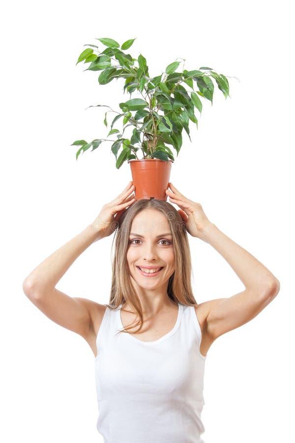 Усмехаясь комнатное растение владением женщины изолированное на белизне стоковое фото